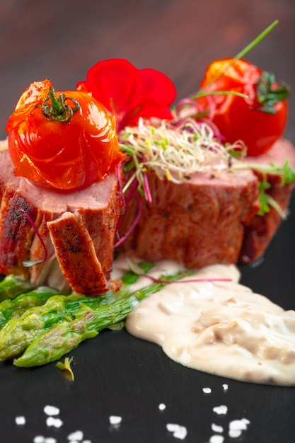 Veal medallions with asparagus on black dishware , wooden table Premium Photo