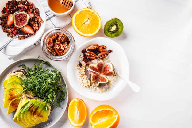 Vegan breakfast table with avocado toast, oatmeal, fruit, on white Premium Photo