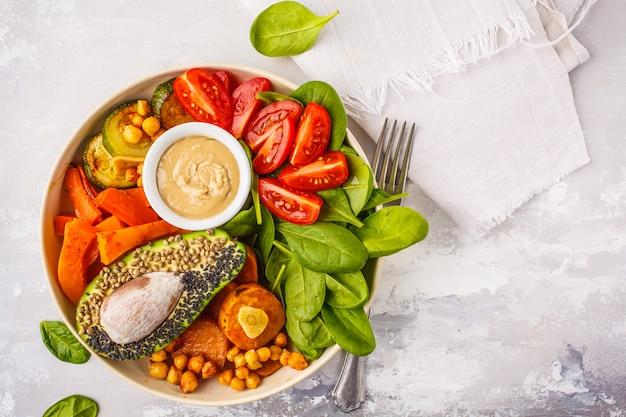 焼き野菜、ひよこ豆、アボカド、ホワイトスペース、上面図、コピースペースにタヒニドレッシングとビーガン仏のボウル。 Premium写真