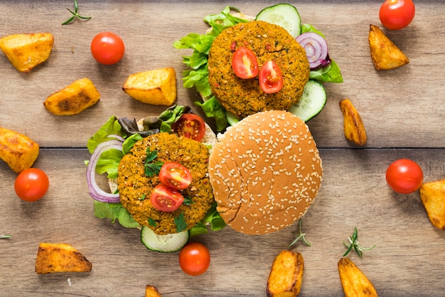 Vegan burgers surrounded by potatoes and tomatoes Free Photo