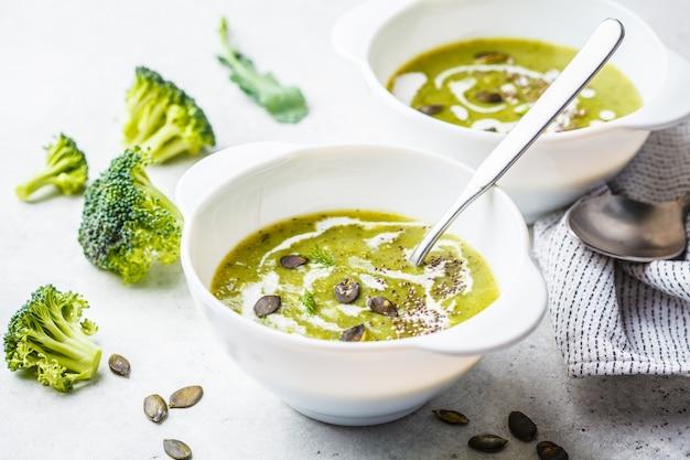 Vegan detox broccoli cream soup with coconut cream and pumpkin seeds in white bowl, copy space. Premium Photo