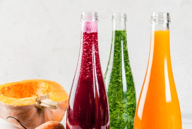 Vegan diet food. selection colorful fresh organic vegetable smoothies with  autumn vegetables: beetroot, pumpkin, carrot, leafy vegetables. in bottles,  with straws, white marble table. copy space | Premium Photo