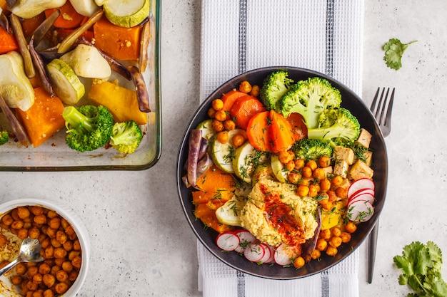 Vegan flat lay, buddha bowl with baked vegetables, chickpeas, hummus and tofu. Premium Photo