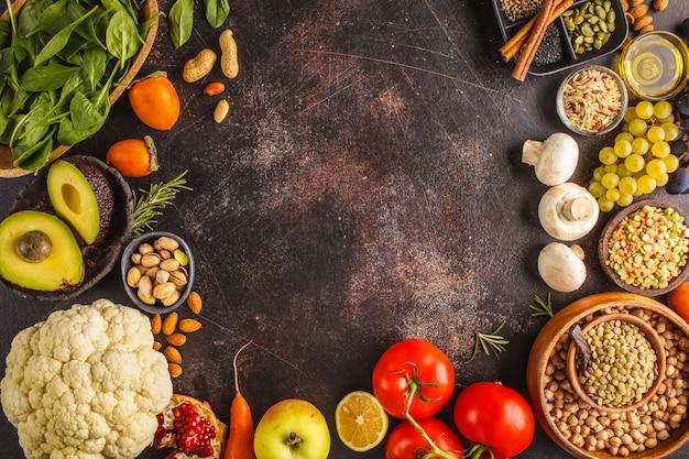 Vegan food ingredients on a dark background. vegetables, fruits, cereals, nuts, beans top view. Premium Photo