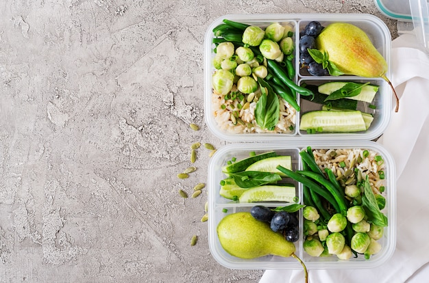 Vegan green meal prep containers with  rice, green beans,  brussel sprouts, cucumber and fruits. dinner in lunch box. top view. flat lay Free Photo