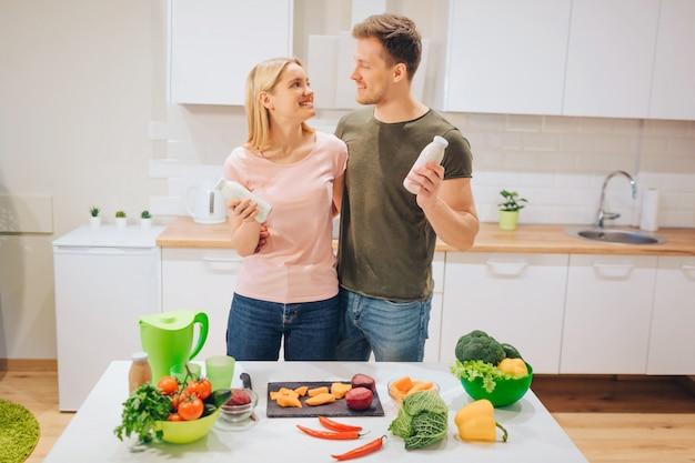 ビーガン幸せな愛情のあるカップルは、白いキッチンで生野菜を調理している間、自然なスムージーのボトルを保持しています。 Premium写真