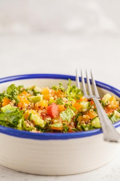 Vegan healthy rainbow salad with quinoa, tofu, avocado and kale. Premium Photo