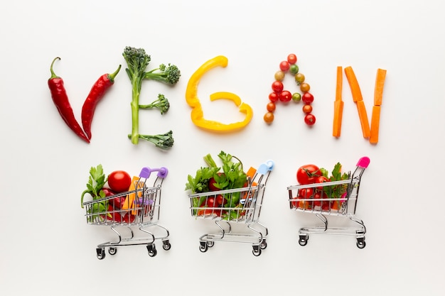 Vegan lettering next to small shopping carts Free Photo