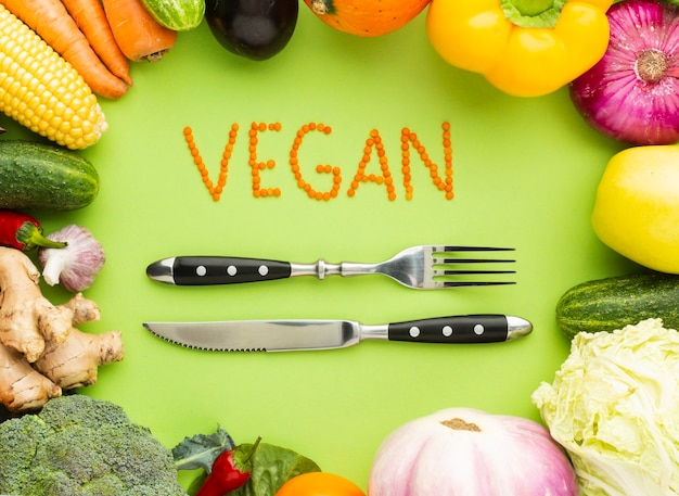 Vegan lettering with fork and knife Free Photo