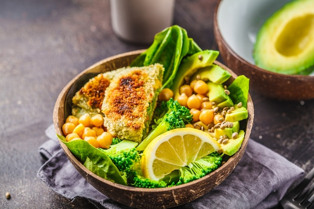 Vegan lunch in a coconut bowl: green burgers with salad and chickpeas. Premium Photo