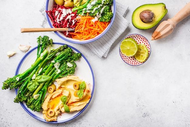 Vegan lunch concept. rainbow vegetable salad and broccolini with hummus. Premium Photo