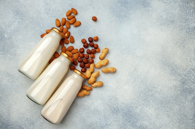 ビーガン非乳製品のナッツミルクと木製の机の上のさまざまなナッツの山 Premium写真