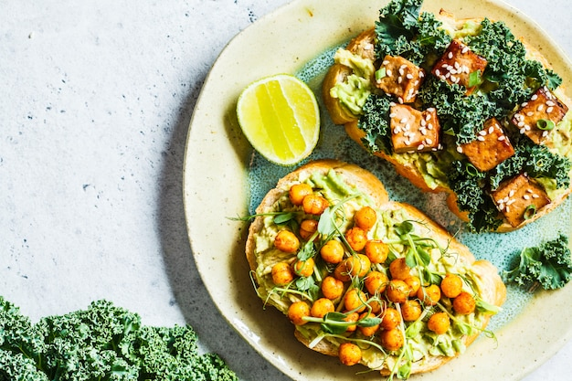 Vegan open sandwiches with guacamole, tofu, chickpeas and sprouts Premium Photo