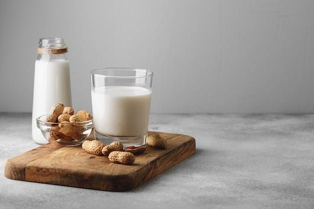 Веганское арахисовое молоко в стакане с арахисом Premium Фотографии