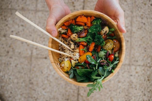 ビーガンの人は健康的な緑、野菜、穀物、箸でいっぱいの木製のココナッツ仏ボウルを持ち上げます。 無料写真