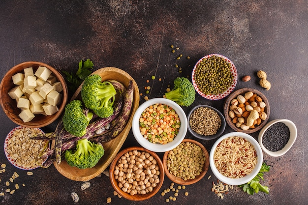 Vegan protein source. tofu, beans, chickpeas, nuts and seeds on a dark background, top view, copy space. Premium Photo