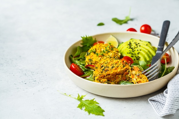 Vegan pumpkin and quinoa cutlets with salad in a white plate. Premium Photo
