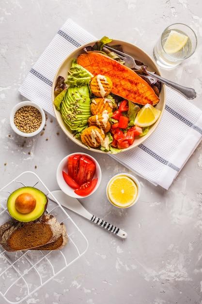 Vegan rainbow bowl of vegetable meatballs, avocado, sweet potato and salad Premium Photo