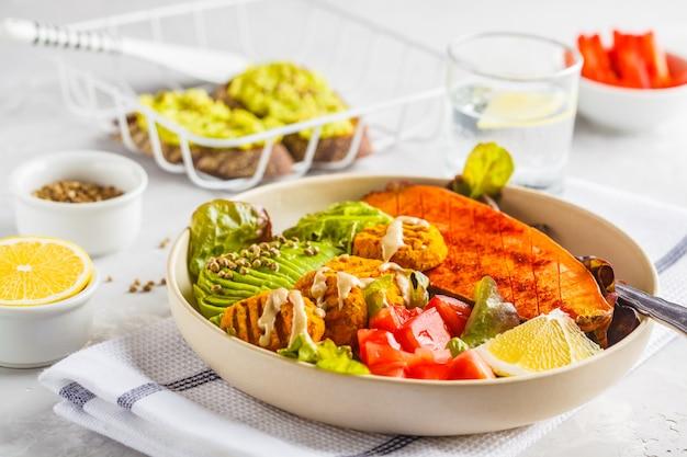 Vegan rainbow bowl of vegetable meatballs, avocado, sweet potato Premium Photo