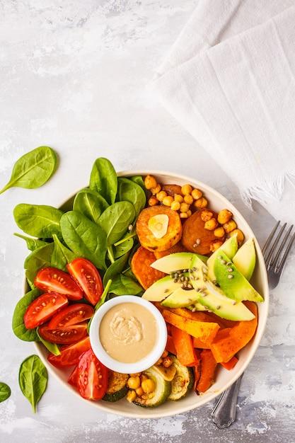焼き野菜、ひよこ豆、アボカド、タヒニドレッシングの白い背景の上のビーガンサラダ Premium写真