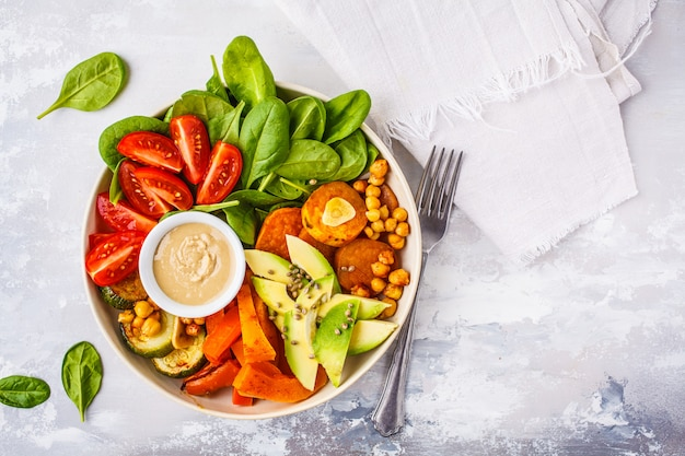 Vegan salad bowl with baked vegetables, chickpeas, avocado and tahini dressing on a white background Premium Photo