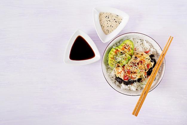 밥에 절인 김치 양배추, 아보카도, 김, 참깨를 넣은 비건 샐러드. 무료 사진