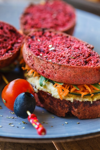 Vegan sandwiches for breakfast with beetroot bread, hummus and vegetables Premium Photo