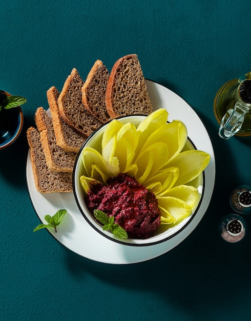 Vegan snack of spread of roasted beets and pistachios and leaves of belgian endive with whole grain bread on the table Premium Photo