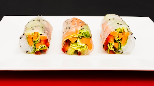 Vegan spring rice paper rolls with vegetables on plate Free Photo