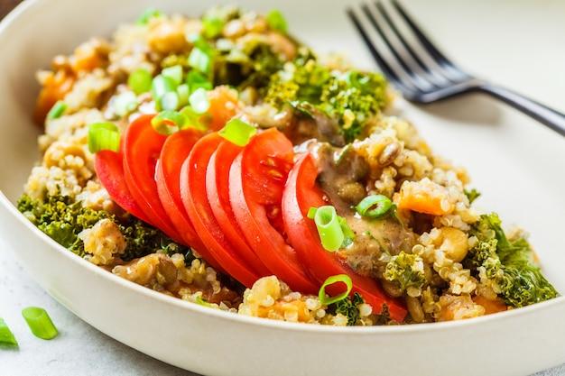 ひよこ豆、さつまいも、白い皿にフレッシュトマトのビーガンシチュー。 Premium写真