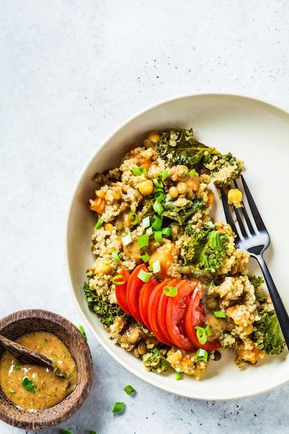 Vegan stew with chickpeas, sweet potato and fresh tomato on a white plate. Premium Photo