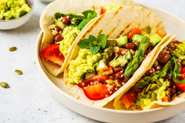 Vegan tortillas with quinoa, asparagus, beans, vegetables and guacamole. Premium Photo