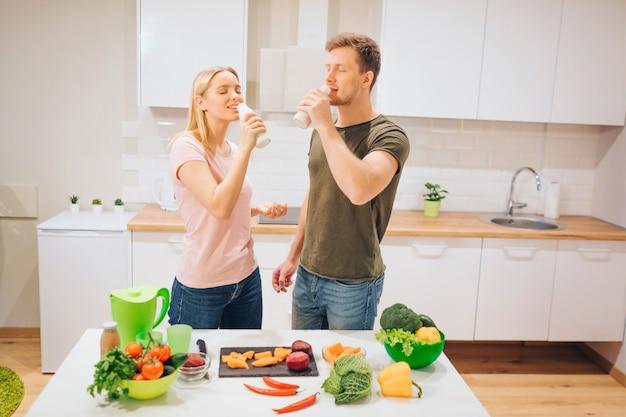 ビーガンの若い愛情のある家族は、キッチンで生野菜を調理しながら自然のスムージーを飲みます。 Premium写真