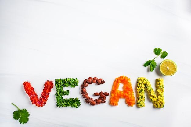 Слово vegan на белой предпосылке, взгляд сверху. веганская еда концепция. веган состоит из бобов, гуакамоле, овощей и трав. Premium Фотографии