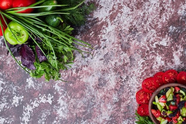 Mix di verdure isolato su un pezzo di marmo con una tazza di insalata da parte in entrambi gli angoli. Foto Gratuite