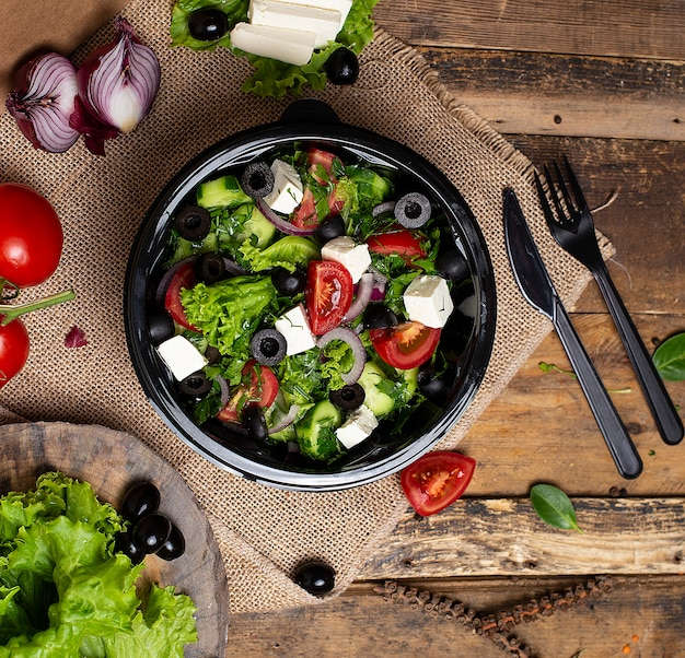Vegetable roka salad with feta white cheese, green salad, tomatoes and olives. Free Photo