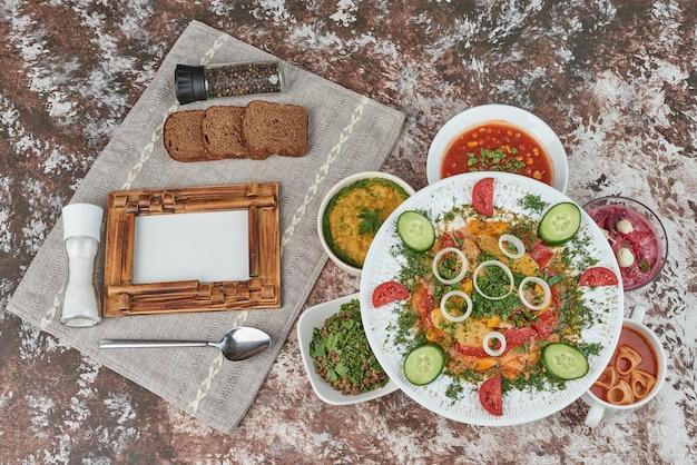 色とりどりの食べ物が入った白いセラミックの盛り合わせの野菜サラダ。 無料写真