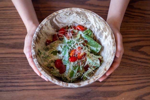 木製のボウルに野菜のサラダ。女性の手は、体に健康的な食品を選び、野菜や果物を食べるサラダを示しています。良い減量ガイドライン。 Premium写真