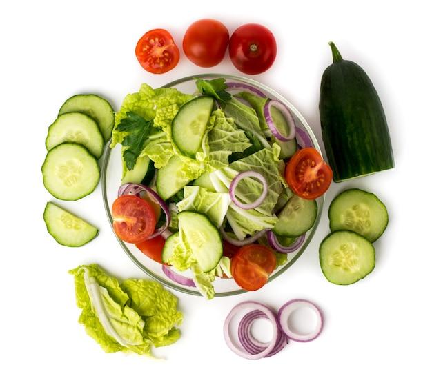 Овощной салат в тарелке и ингредиенты, с которыми он сделан на белом. вид сверху. Premium Фотографии
