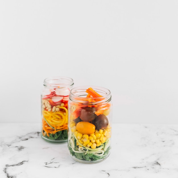 Vegetable salad in an open mason jar on marble top against white background Free Photo