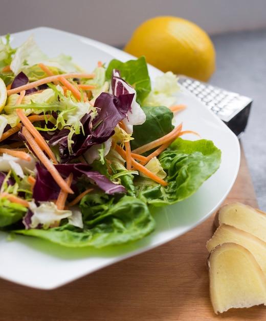 Vegetable salad on plate with lemon on table Free Photo