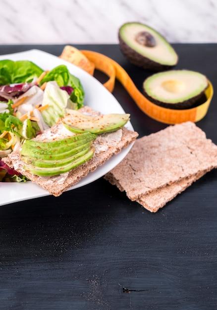 Vegetable salad with avocado on crisp bread on table Free Photo