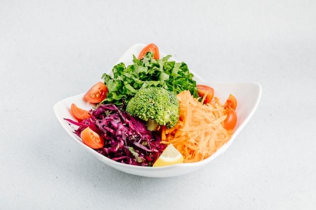 キャベツのみじん切り、ニンジン、トマトのスライス、レタス、ブロッコリーの野菜サラダ。 無料写真