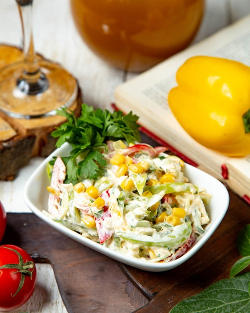 Vegetable salad with corn dressed with mayonnaise Free Photo
