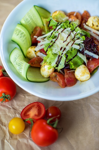 Vegetable salad with lettuce, boiled tomato, cucumber and mushroom with grated cheese Free Photo
