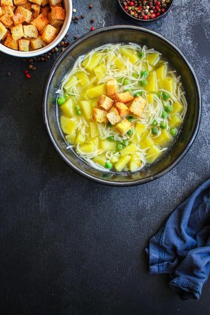 野菜スープグリーンピースと小さな薄いパスタ Premium写真