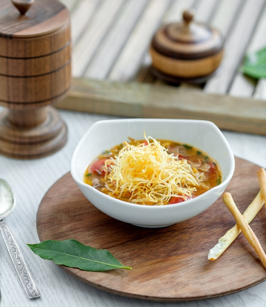 Vegetable soup topped with potato shoestrings served with bread sticks Free Photo