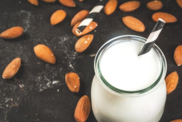 Растительные источники белка. веганская здоровая пища. маленькая бутылка порции миндального молока. на фоне орехов миндаль на черном бетонном столе. выборочный фокус. Premium Фотографии