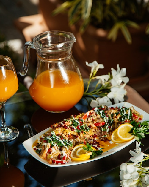 Vegetable stew garnished with herbs and lemon, served with orange juice Free Photo