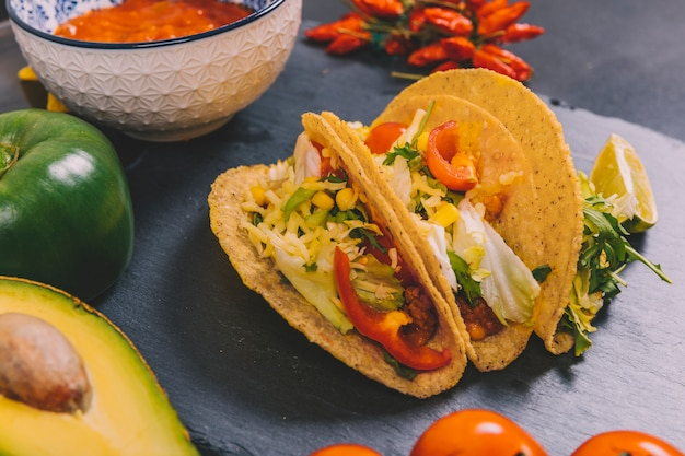 Vegetables; avocado with mexican beef tacos on black slate Free Photo